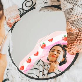 woman applying apple cider vinegar resurfacing pad in mirror