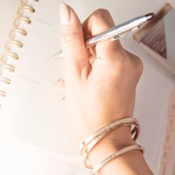 woman writing and wearing rose gold cuff