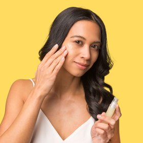 woman applying Daily Vitamin Glow Booster to face