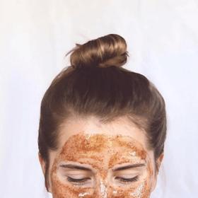 woman with bun wearing turmeric brightening polish