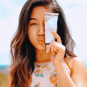 woman holding turmeric brightening polish