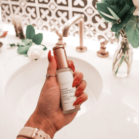 hand holding snow mushroom water serum above sink