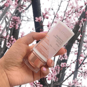 hand holding prismatic luminizing shield spf 50 in front of cherry tree