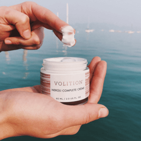 hand holding neroli complete creme near water