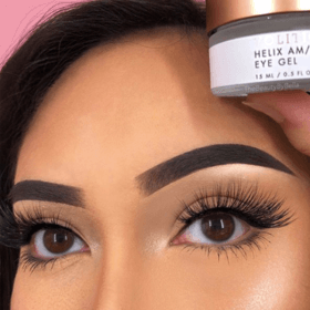 woman with full face makeup holding Helix AM/PM Eye Gel