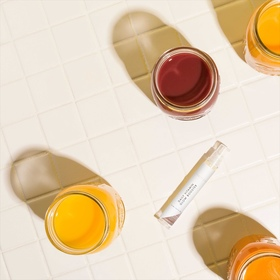 Daily Vitamin Glow Booster with juice on tiles