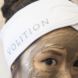 close up of woman wearing mask and splash headband and detoxifying silt gelee