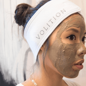 woman wearing mask and splash headband and detoxifying silt gelee