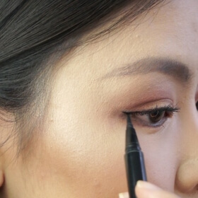 woman lining her eyes with Double Edged Eyeliner Pen