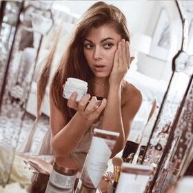 woman applying Illuminating Body Milk in mirror